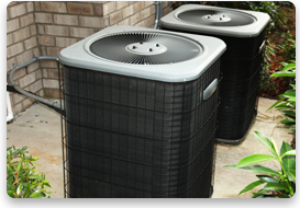 A pair of moderate siced air conditioning units surrounded by bushes.